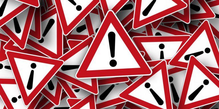 Grafika przedstawiająca duży stos ostrzegawczych znaków drogowch z wykrzyknikiem.